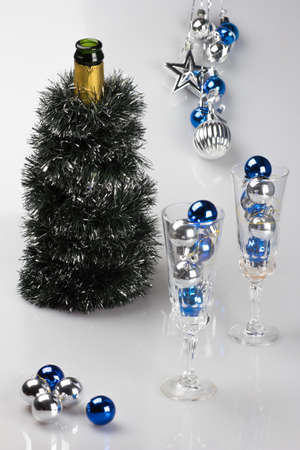 Decorated bottle of champagne and glasses filled with Christmas toys. photo
