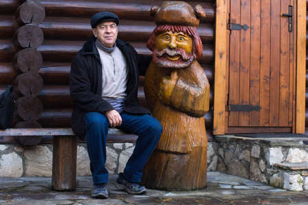 Elderly man sitting on a bench close to a wooden statue in the yard photo