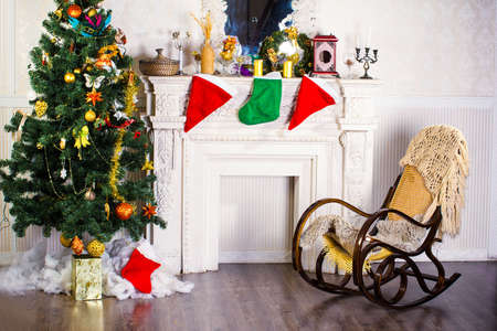 Rocking chair and Christmas tree near the fireplace photo