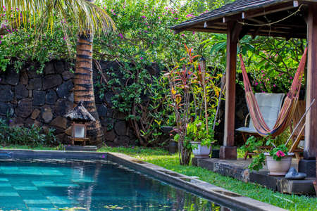 Garden house, hammock and chair on a tropical greenery photo