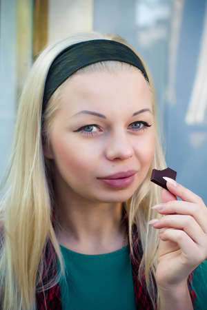 Beautiful blond girl eating a piece of chocolate photo