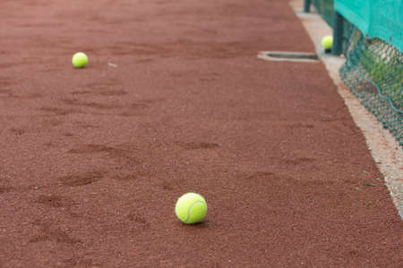 beat the competition: Three green tennis balls on the clay court