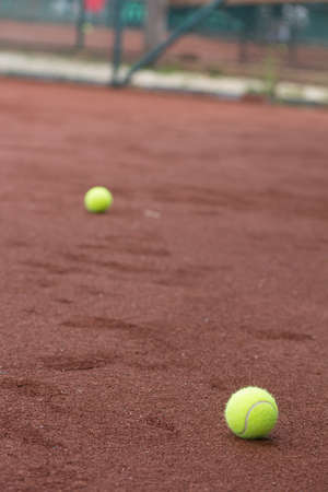 beat the competition: Two green tennis balls on the clay court Stock Photo