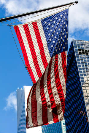 urbanistic: Bright american flag and the skyscrappers in a sunny weather