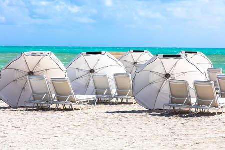 sun umbrellas: Sun umbrellas on the beach of ocean. Miami Beach, Florida. Stock Photo