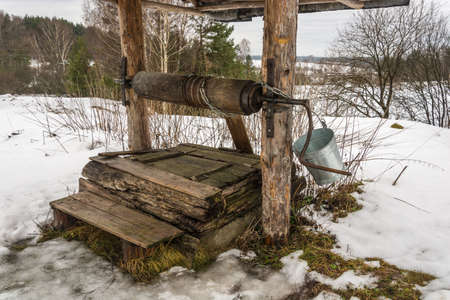 The old wooden well on the edge of the village with a metal bucket for water lifting   photo