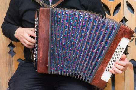 widely: Accordionist plays Russian accordion, widely stretching fur. Stock Photo
