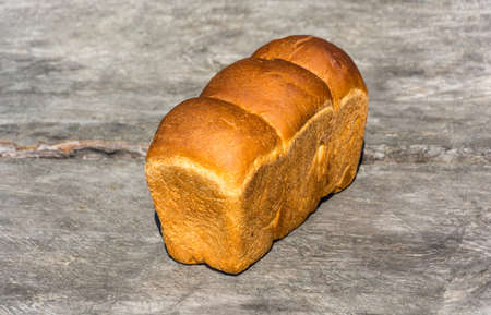 life loaf: Golden loaf of wheat bread on a gray background.