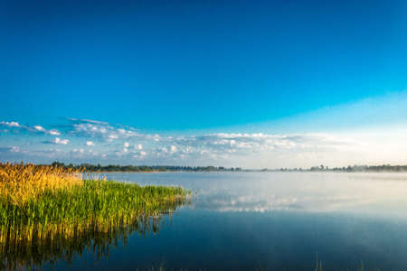 uprise: The quiet early morning on the lake. Cumulus clouds are reflected in the mirrored surface of the water. Stock Photo