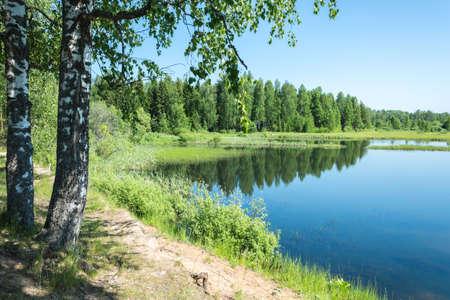 Mooi landschap met een meer. In de spiegel oppervlak van het water weerspiegelt de blauwe hemel. Stockfoto