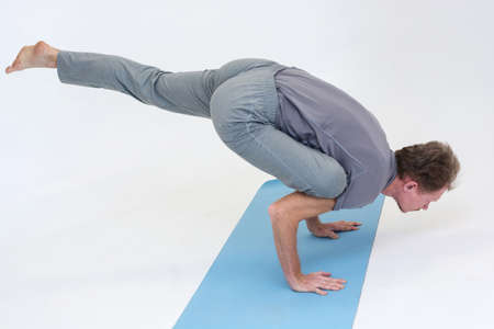 hatha: Man performs asanas of Hatha yoga on a blue mat and white background. Stock Photo