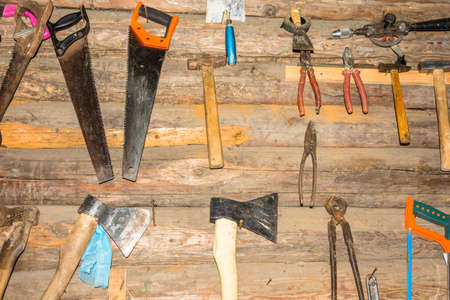 log wall: Various tools on the log wall: saw hammer axe drill passatge scissors.