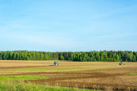 spaciousness: Large plowed field framed by the green of a forest on a Sunny day.