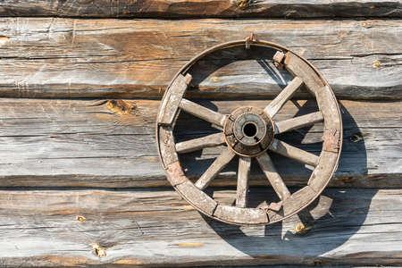 carreta madera: Gran rueda de carro de madera en el fondo de las paredes de troncos.