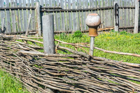 yard stick: A clay jug hanging on a stick in the yard of a village house.