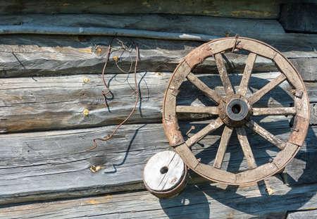 carreta madera: Las grandes ruedas de carro de madera en el fondo de las paredes de troncos.