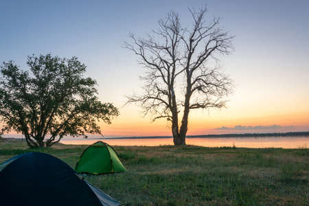 the volga river: Early morning on the banks of the Volga river. In the foreground tourist tents. Stock Photo