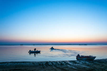 uprise: Early morning on the Volga river. In the foreground motor boats with fishermen. Stock Photo