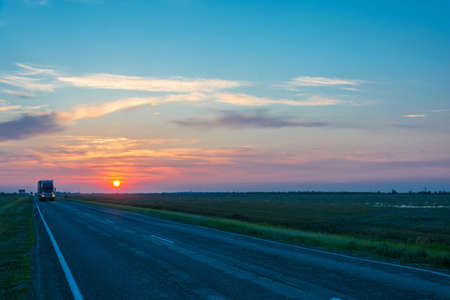 spaciousness: Beautiful red sunset. In the foreground the road with cars.