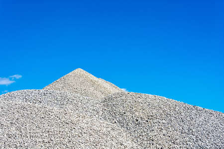 Mountain grey crushed stone against the bright blue sky. Stok Fotoğraf