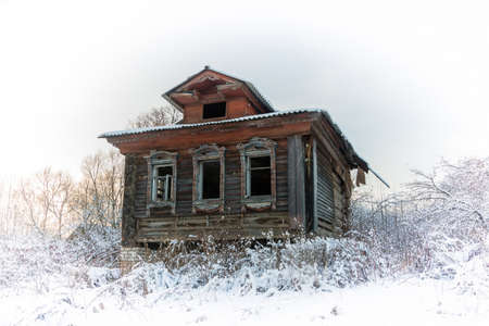 grass: Abandoned village house on a winter background.