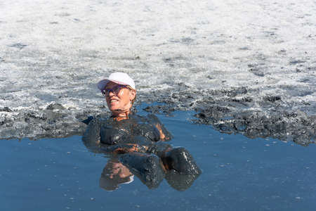 curative: The woman take the curative mud baths of lake Elton, Volgograd region, Russia.