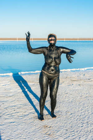 curative: The woman take the curative mud baths on the lake Baskunchak, Astrakhan region, Russia.