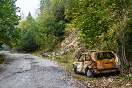 detriment: Burnt car stands on the side of mountain roads in Abkhazia.