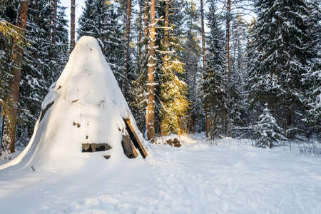 The old wigwam, covered with snow in the rays of the setting sun.