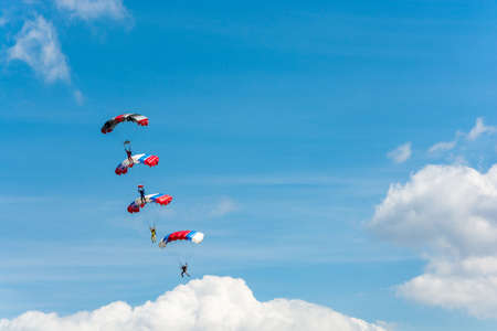 Parachutists descending on the background of beautiful cloudy sky on a Sunny day.