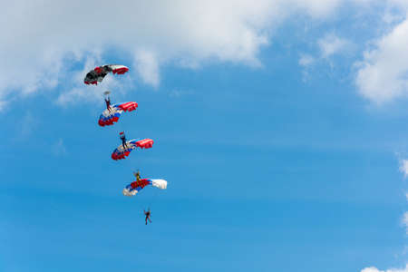 parachutists: Parachutists descending on the background of beautiful cloudy sky on a Sunny day.