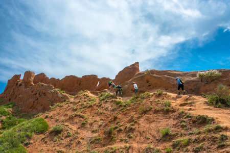A group of tourists climbs a steep hill in the canyon at Fairy Tale, Kyrgyzstan.