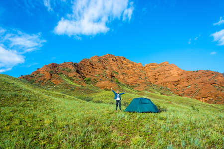 kyrgyzstan: A young woman in a blue tent on a background of orange mountains and green grass, Eolian mountains, Kyrgyzstan.
