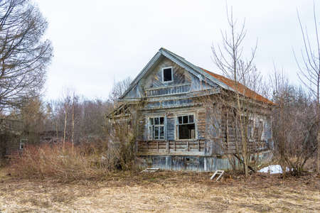 Abandoned old wooden house in the spring cloudy day. Stock Photo