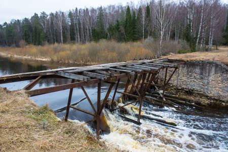 The dilapidated bridge over the small tumultuous river on a cloudy April day.