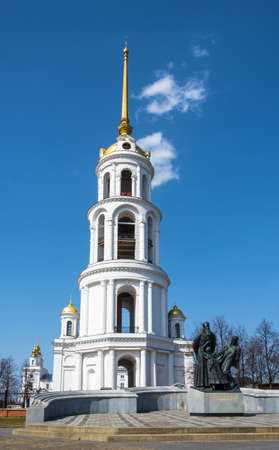 A monument to the new martyrs of Russia on the background of the tall white bell tower in Shuya, Ivanovo oblast, Russia. Stock Photo
