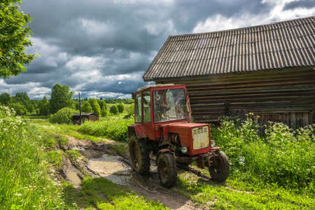 Wheel tractor on a country road in the summer cloudy day.