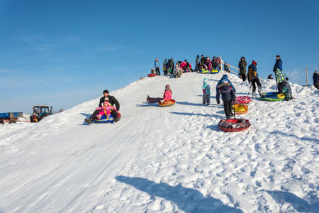 Uglich city, Yaroslavl region, Russia - 10.02.2018: Riding from the snow slide at the festival Winter fun in Uglich, 10.02.2018 in Uglich, Yaroslavl region, Russia.
