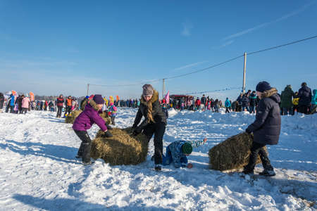 City of Uglich, Yaroslavl region, Russia - 10.02.2018: Merry competition for hay carrying at the festival Winter fun in Uglich, 10.02.2018 in Uglich, Yaroslavl region, Russia.