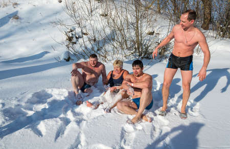 City of Uglich, Yaroslavl region, Russia - 10022018: Undressed men and a woman are lying on snow-white fluffy snow, at the festival Winter fun in Uglich, 10.02.2018 in Uglich, Yaroslavl region, Russia.