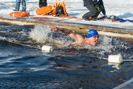 Uglich city, Yaroslavl region, Russia - 10022018: Competitions in swimming in icy water, at the festival Winter fun in Uglich, 10.02.2018 in Uglich, Yaroslavl region, Russia.
