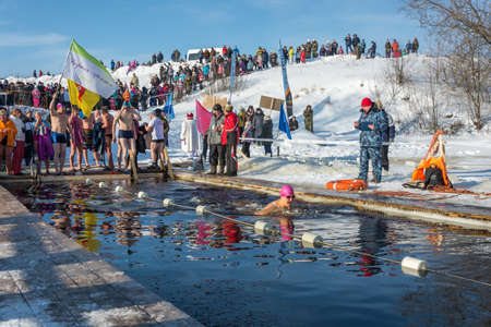 Uglich city, Yaroslavl region, Russia - 10.02.2018: Competitions in swimming in icy water, at the festival Winter fun in Uglich, 10.02.2018 in Uglich, Yaroslavl region, Russia. Редакционное