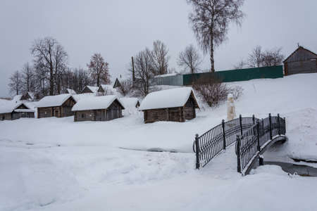 Wooden baths on black, standing on the bank of a small river on a winter day in the village of Vyatskoe, Russia.