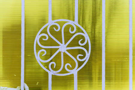 Beautiful curly white metal fence on a yellow striped background.