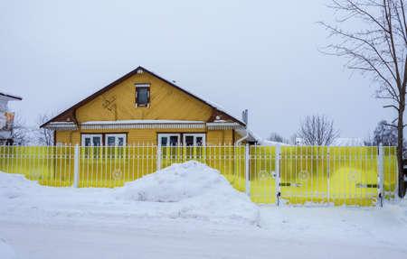 Village Vyatskoe, Yaroslavl region, Russia - February 17, 2018: A small wooden house with a bright yellow fence February 17, 2018 in the village of Vyatskoye, Yaroslavl region, Russia.
