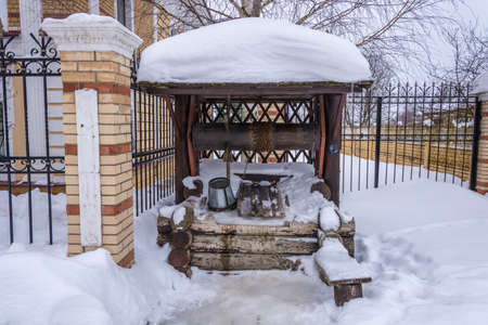 A wooden well with a metal bucket and chain on a winter day.