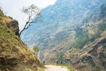 Tourists on a mountain road in the Himalayas on a trek around the Annapurna, Nepal.
