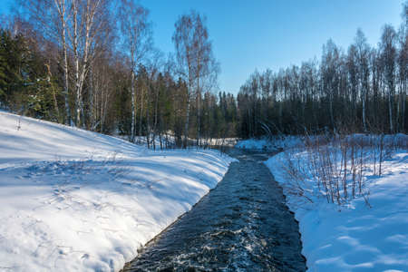 A narrow, raging river on snowy shores on a Sunny winter day.