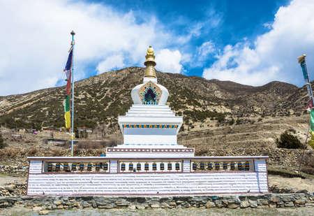 Large white stone Buddhist stupa in a mountain village in the Himalayas, Nepal. Фото со стока