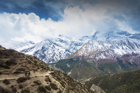 Tourists on a beautiful mountain trail in the Himalayas. Snowy peaks in the clouds, Nepal.
